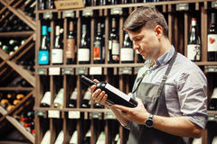 Young sommelier holding bottle of red wine in cellar Stock Images