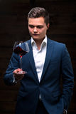 Young sommelier looking at red wine. Sommelier in suite looking at red wine. Caucasian businessman looking at the Glass of Red Wine. Confident businessman looks Stock Images
