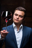 Young sommelier looking at red wine. Sommelier in suite looking at red wine. Caucasian businessman looking at the Glass of Red Wine. Confident oligarch looks at Stock Images
