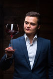 Young sommelier looking at red wine. Sommelier in suite looking at red wine. Caucasian businessman looking at the Glass of Red Wine. Confident oligarch looks at Stock Photos