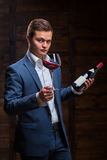Young sommelier looking at red wine. Sommelier in suite looking at red wine. Caucasian businessman looking at the Glass of Red Wine. Confident oligarch looks at Royalty Free Stock Photo
