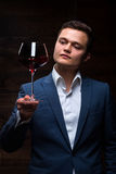 Young sommelier looking at red wine. Sommelier in suite looking at red wine. Caucasian businessman looking at the Glass of Red Wine. Confident oligarch looks at Royalty Free Stock Images