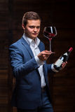 Young sommelier looking at red wine. Sommelier in suite looking at red wine. Caucasian businessman looking at the Glass of Red Wine. Confident oligarch looks at Royalty Free Stock Image