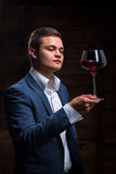 Young sommelier looking at red wine. Sommelier in suite looking at red wine. Caucasian businessman looking at the Glass of Red Wine. Confident oligarch looks at Royalty Free Stock Photos