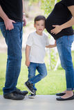 Young Son With Ear on Pregnant Belly of Mommy. Courious Young Mixed Race Son With Ear on Pregnant Belly of Mommy with Daddy Nearby Royalty Free Stock Photography