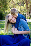 Young son embracing mother while having fun sitting outdoors - l. Ooking away from camera - wearing casual blue denim clothes stock photo