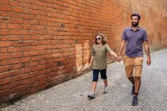 Young son and father walking together along cobblestone streets royalty free stock photo