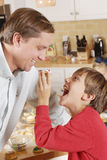 Young son feeding dad a cookie in the kitchen. Young son feeding dad a cookie with frosting in the kitchen, Fun and playful after cooking with the whole family Royalty Free Stock Photo