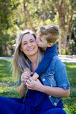 Young son kissing mother on cheek while having fun sitting outdo. Ors - wearing casual blue denim clothes royalty free stock photos