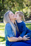 Young son kissing Mother on cheek whilst sitting outdoors in par. K - looking away from camera stock image