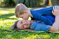 Young son kissing Mother whilst playing on rug in park. Mother looking at camera royalty free stock images
