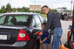 Young son looking at father refilling car Stock Photo
