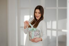 Young sophisticated woman openinga present box. Surprised happy young woman in elegant white interior home, holding a beautiful present round box, pulling the Stock Images