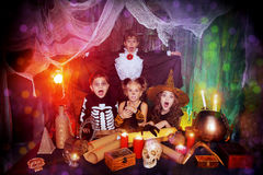 Young sorceress. Group of frightened children dressed in halloween costumes in a wizarding lair. Halloween party royalty free stock image