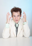 Young sorrowful man in white suit sits at table Royalty Free Stock Images