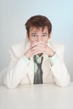 Young sorrowful person in white suit sits at table Royalty Free Stock Photo