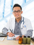 Asian medical doctor working on his desk royalty free stock image