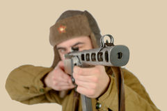 A young Soviet soldier fires with a machine gun Royalty Free Stock Images