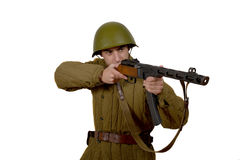 Young Soviet soldier shoots with his ppsh 41. He have a helmet stock image