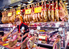 Young spanish dealer slicing iberico and serrano jamon. SPAIN, BARCELONA, JUNE, 29, 2015 - Young spanish dealer slicing iberico and serrano jamon, hanging on the Stock Photography