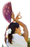 Young Spanish female dancer with Spanish fan. Young traditional Spanish female flamenco dancer with long brown hair and holding fan in the sun Royalty Free Stock Image