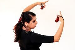 Young Spanish gipsy woman dancing flamenco with brown castanets. Royalty Free Stock Photography