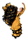 Young Spanish woman dancing flamenco in typical folk tailed gown dress. Young spanish woman dancing Sevillanas wearing typical folk gold and black  tailed gown Royalty Free Stock Photos