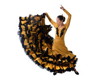 Young Spanish woman dancing flamenco in typical folk tailed gown dress. Young spanish woman dancing Sevillanas wearing typical folk gold and black  tailed gown Stock Photography