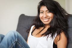 Young Spanish woman smiling and relaxing on a sofa. Home stock photos