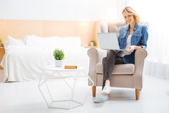 Cheerful young specialist smiling while having a productive day at home. Young specialist. Positive emotional young woman sitting in a comfortable beautiful room Stock Image
