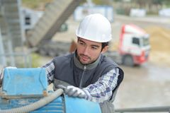 Young specialist using steel bending machine. Buider Stock Images