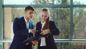 Young specialists conduct a business conversation, use a tablet. Stand at the big window in the office stock video footage