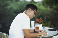 Young spectacled man drinking cold beer and writing some notes in notebook. stock photography