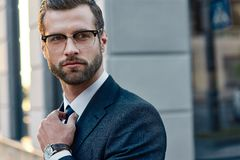 The young in spectacles men straightens his tie, his face unshaven royalty free stock photography