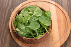 Young spinach in a wooden plate Royalty Free Stock Photo