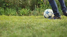 Young sport boy playing with soccer ball kicks on the grass in summer sunny day in slow motion. 1920x1080. hd stock video footage