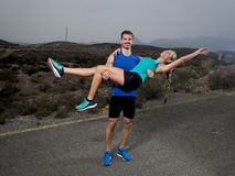 Young sport couple happy together outdoors on mountain landscape man holding girl on his strong arms having fun Royalty Free Stock Photos