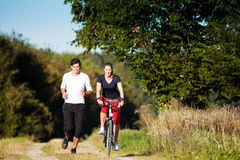 Young sport couple jogging and cycling. Young fitness couple doing sport outdoors, jogging on a green summer meadow in the grass under a clear blue sky Royalty Free Stock Photo