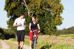 Young sport couple jogging and cycling. Young fitness couple doing sport outdoors, jogging on a green summer meadow in the grass under a clear blue sky Royalty Free Stock Image