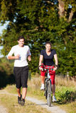 Young sport couple jogging and cycling stock images