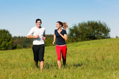 Young sport couple jogging outdoors in summer. Young fitness couple doing sport outdoors, jogging on a green summer meadow in the grass under a clear blue sky Stock Photo