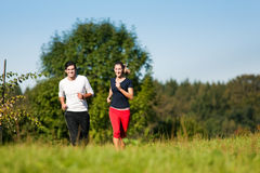 Young sport couple jogging outdoors in summer. Young fitness couple doing sport outdoors, jogging on a green summer meadow in the grass under a clear blue sky Stock Images