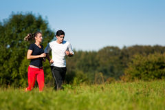 Young sport couple jogging outdoors in summer. Young fitness couple doing sport outdoors, jogging on a green summer meadow in the grass under a clear blue sky Stock Photography