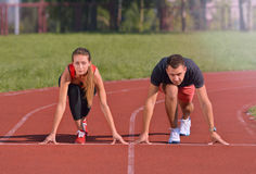 Young sport couple in starting position prepared to compete. Looking ahead. Healthy fitness concept with active lifestyle Royalty Free Stock Photos