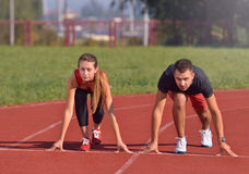 Young sport couple in starting position prepared to compete and run Royalty Free Stock Images