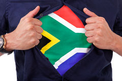Young sport fan opening his shirt and showing the flag his count stock photo