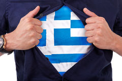 Young sport fan opening his shirt and showing the flag his count. Ry Greece, Greek flag Royalty Free Stock Image