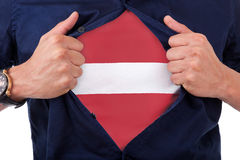 Young sport fan opening his shirt and showing the flag his count Stock Image