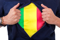 Young sport fan opening his shirt and showing the flag his count. Ry Mali,  Malian flag Royalty Free Stock Photography