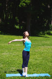 Young sport girl do yoga in the park. Royalty Free Stock Image
